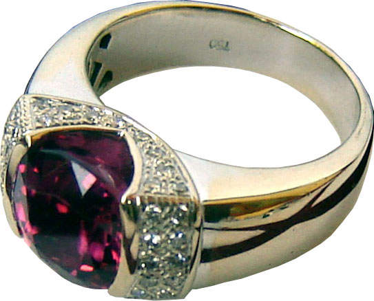 Ring with a large cushion cut rhodolite garnet in the center with diamonds on either side.