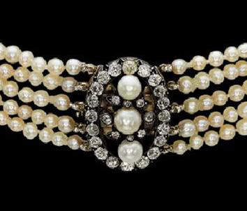 A close up of the clasp of the 5 row antique natural pearl and diamond necklace